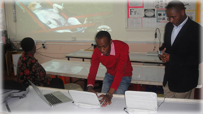 An associate from Kijani at the NGSA main computer lab assists the teachers set up equipment in readiness for Skype interactions